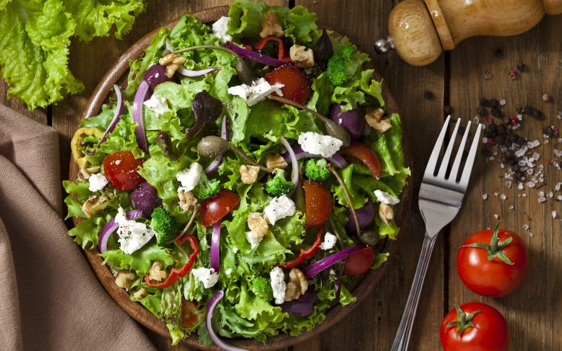 Top view of a colorful spring salad on rustic wood table. The ingredients included in the salad are lettuce, radicchio, spanish onion, black olives, capers, broccoli, bell pepper, walnut and goat cheese. The salad is served on a wood plate and a fork is beside it. A pepper grinder is tilted coming from the upper-right side of the frame and a textile napkin is at the lower-left of the frame.  DSRL studio photo taken with Canon EOS 5D Mk II and Canon EF 70-200mm f/2.8L IS II USM Telephoto Zoom Lens